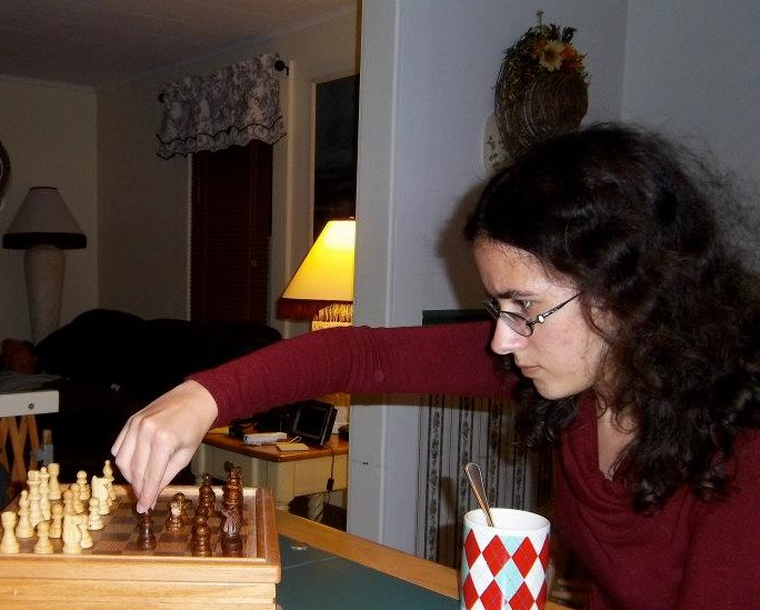 Picture is of author making a move in chess. Hair is messy, face is intense. She is very focused on the game.