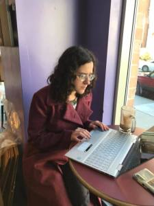 Picture of author writing on a laptop, in a coffee shop, wearing a long red coat. There is a coffee beside her on the table.