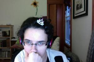 Photo is of the author staring, exhausted, into the computer camera. She has a tiny plastic tiara stuck, crooked, into her very messy hair.