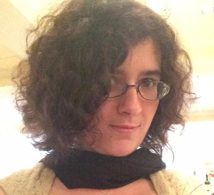 Photo of author with neat, curly hair, lip gloss on her lips, and a scarf around her neck. The effect is polished, put-together.